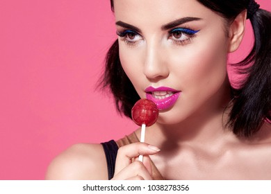 Close portrait of sexy beautiful woman brunette hair style perfect bright makeup mascara pink lipstick background face care cosmetic accessory jewelry sweets lollipop diet beauty salon white teeth.