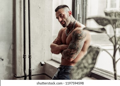 Close up portrait of Sexy naked male model with tattoo and magic eyes standing in hot pose on near the window. Loft room interior with grey concrete wall. Professional Studio image.