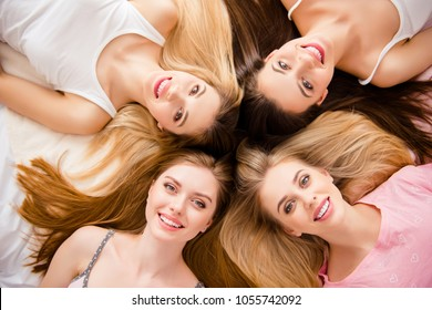 Close up portrait of sexy, pretty, crazy, sweet, charming, funny, foolish, blonde, brunette, lovely, cheerful girls lying head to head on bed looking at camera