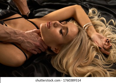 Close up portrait of a sexy young blonde with beautiful curly hair. Male hand touches.