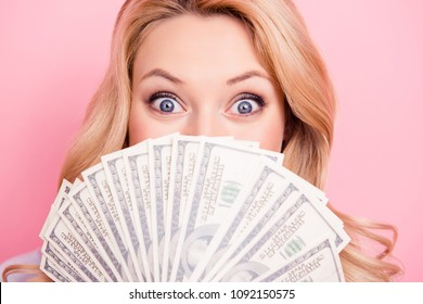 Close up portrait of shocked surprised girl peeking out fan of much money with wide open eyes hiding her half face isolated on pink background