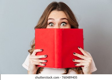 Close up portrait of a shocked young girl hiding behind an open book isolated over gray wall background