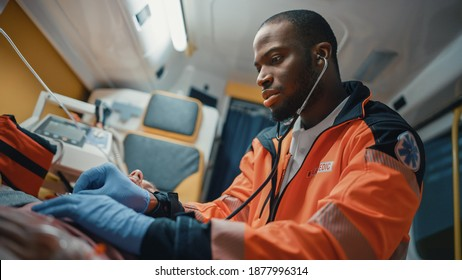 Close Up Portrait Shot of an African American Professional Paramedic Providing Medical Help to an Injured Patient on the Way to Hospital. Emergency Care Assistant Using Stethoscope in an Ambulance.