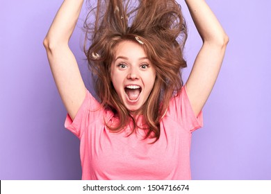 Close up portrait shot of playful young female jumping high, shouting loudly, messy hair upwards, suprised and happy to get present, dreams come true, birthday girl, modeling over light purple wall.