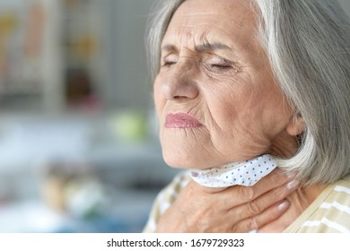 Close up portrait of sick senior woman posing at home with sore throat
