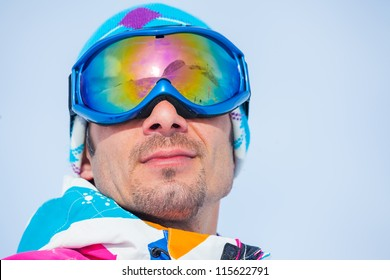Close up portrait of the ski goggles of a man with the reflection of snowed mountains
