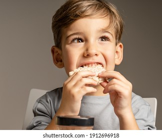 Close up portrait of small caucasian boy four years old eating Crispy puffed rice cake looking to the side - healthy gluten free vegan or vegetarian food - front view studio shot