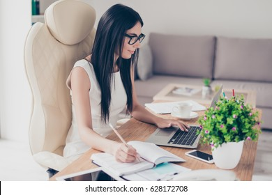 Close up portrait of smart brunette girl in glasses browsing info in laptop and writing it down in notebook at nice modern office