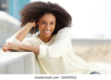 Close up portrait of a smiling african american woman with curly hair sitting outdoors