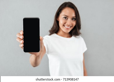 Close up portrait of a smiling asian woman showing blank screen mobile phone while standing isolated over gray background