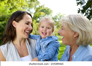 Close up portrait of a smiling baby with mother and grandmother