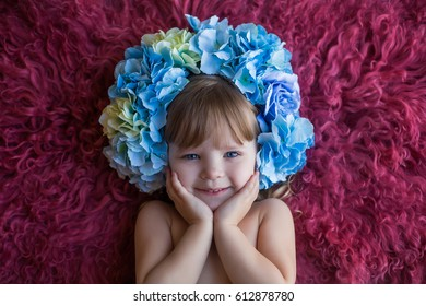 close up portrait of smiling baby on purple fur background in flower hydrangea wreath spring easter inspiration