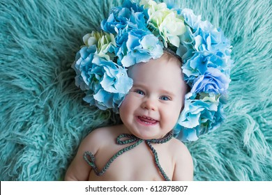 close up portrait of smiling baby on light blue fur background in flower hydrangea wreath spring easter inspiration