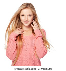 Close up portrait of smiling beautiful blond female in pink sweater with hair lightly fluttering in the wind, over white background