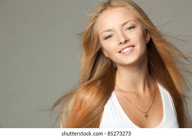 Close up portrait of smiling beautiful blond female with hair lightly fluttering in the wind