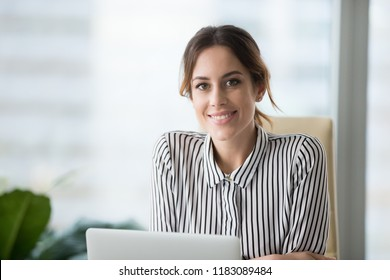Close up portrait of smiling beautiful millennial businesswoman or CEO looking at camera, happy female boss posing making headshot picture for company photoshoot, confident successful woman at work
