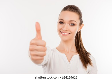 Close up portrait of smiling beautiful woman giving a thumb up as a sign of recommendation
