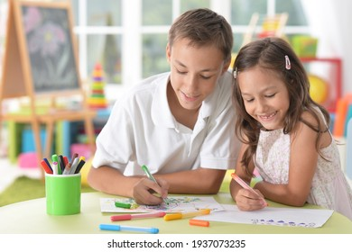Close up portrait of smiling brother and sister drawing together