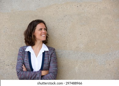 Close up portrait of a smiling business woman standing with arms folded looking away