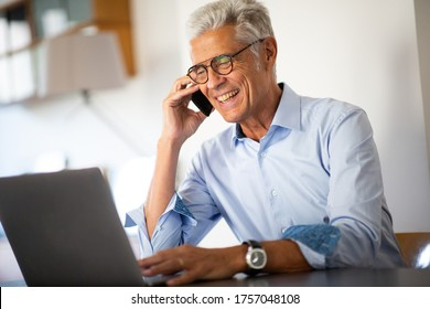 Close up portrait smiling businessman talking with phone while looking at laptop computer