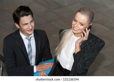 Close up portrait of smiling businesswoman with smart phone and partner.