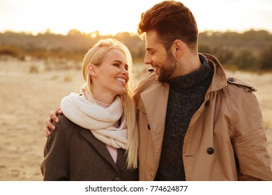 Close up portrait of a smiling couple in love hugging while walking along the beach
