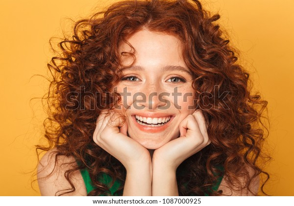 Close up portrait of a smiling curly redhead woman looking at camera isolated over yellow background