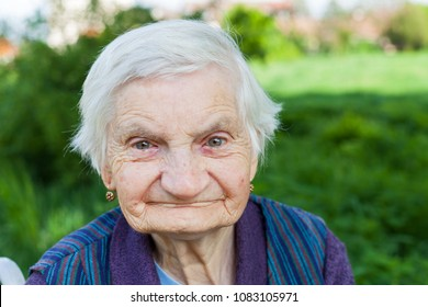 Close up portrait of smiling elderly woman suffering from dementia disease, outdoor