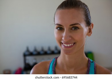 Close up portrait of smiling female athlete in gym