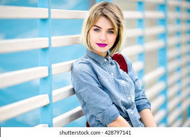 Close portrait of a smiling girl with short blond hair, bright pink lips and nude make up leaning on blue and white stripes fence on the background and wearing blue denim shirt