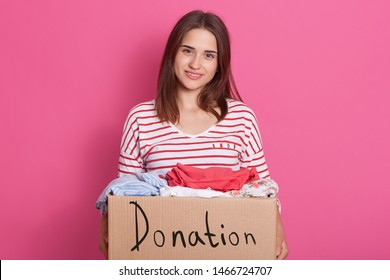 Close up portrait of smiling girl volunteering holding paper box with clothes for poor people, lady making donation, female wears stylish outfits posing and looking directly at camera. Charity concept