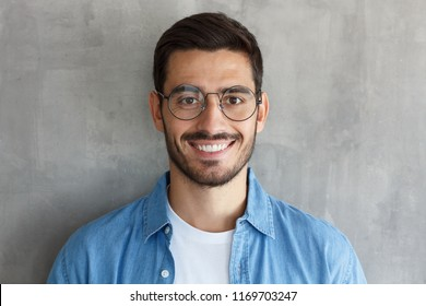 Close up portrait of smiling handsome man in round glasses and blue shirt isolated on gray textured wall