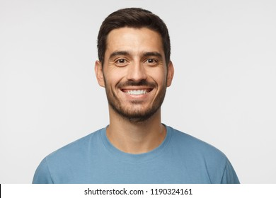 Close up portrait of smiling handsome man in blue t-shirt isolated on gray background