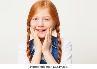 Close up portrait of smiling happy adorable girl with braided red hair in two long plaits, keeps palms near her face, dressed in jeans overall isolated on white background