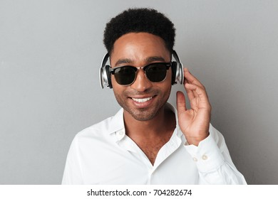 Close up portrait of a smiling happy african man in sunglasses enjoys listening to music with headphones isolated over gray background