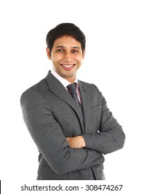 Close up portrait of a smiling Indian business man with arms crossed isolated on white.