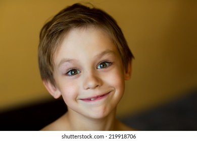 A close up portrait of a smiling little boy with a pursy mouth
