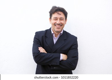 Close up portrait of a smiling mature businessman posing with arms crossed against white background