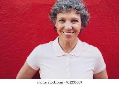 Close up portrait of smiling mature woman against red background. Middle aged woman with beautiful smile.