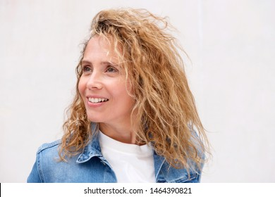 Close up portrait of smiling middle age woman with curly hair against white wall