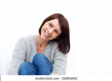 Close up portrait of a smiling middle aged woman sitting against white wall