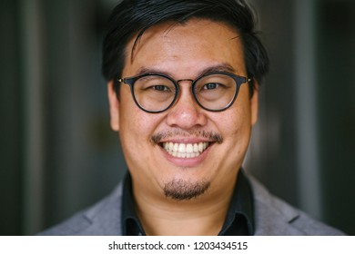 A close up portrait of a smiling middle-aged Chinese Asian man in a black shirt, grey suit, glasses and pocket square. He has short hair.
