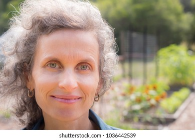 Close up portrait of smiling natural looking middle aged woman with grey hair in garden (selective focus)