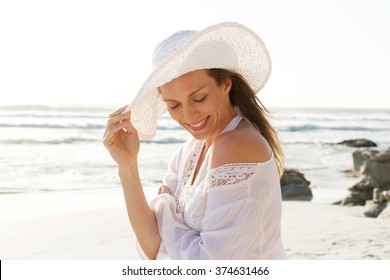 Close up portrait of a smiling older woman with hat at the beach