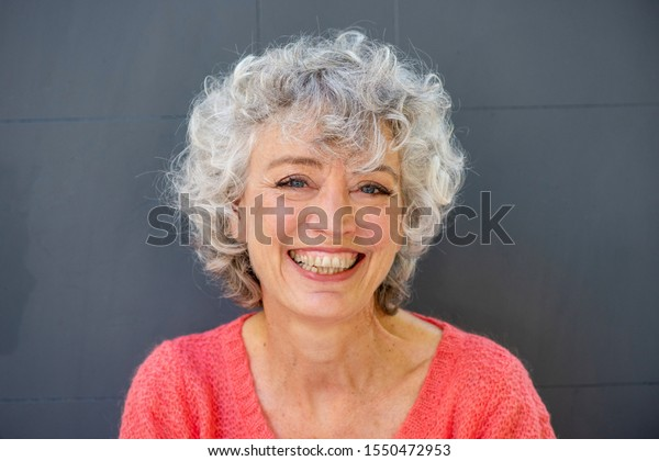 Close up portrait of smiling older woman against gray background
