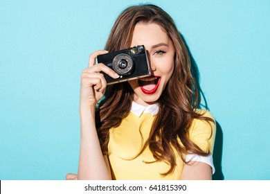 Close up portrait of a smiling pretty girl in dress taking photo on a retro camera isolated over blue background