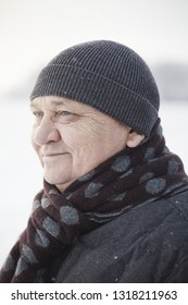 Close up portrait of smiling senior man wearing knit cap, scarf and jacket standing outdoors in winter