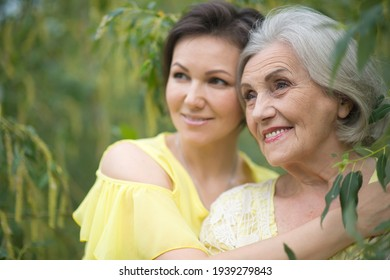 Close up portrait of smiling senior woman with adult daughter in autumnal park