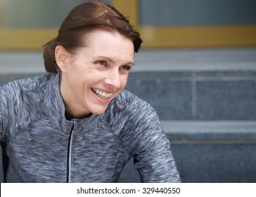 Close up portrait of a smiling sporty woman sitting outside