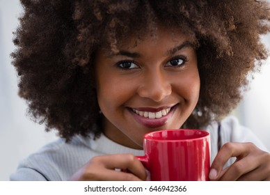 Close up portrait of smiling woman with frizzy hair holding coffee mug in cafe